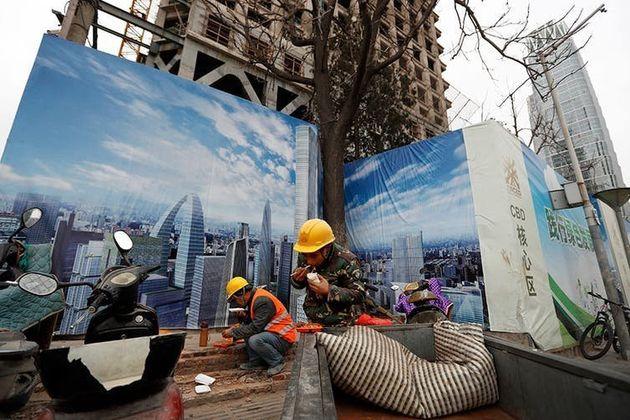 Trabalhadores almoçam em canteiro de obras no Distrito Central de Negócios de Pequim, diante de um mural...