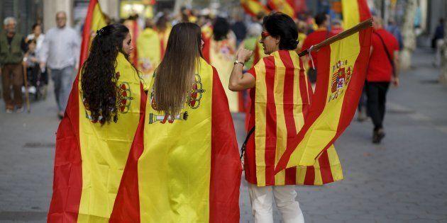 Pessoas usando as bandeiras da Espanha e da Catalunha andam
