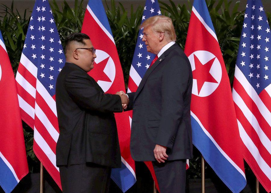 Donald Trump e Kim Jong-un se cumprimentam no Hotel Capella, na ilha de Sentosa, em