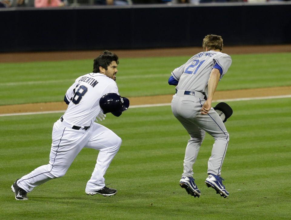 San Diego Padres' Carlos Quentin charges into Los Angeles Dodgers pitcher Zack Greinke after being hit by a pitch in the sixt