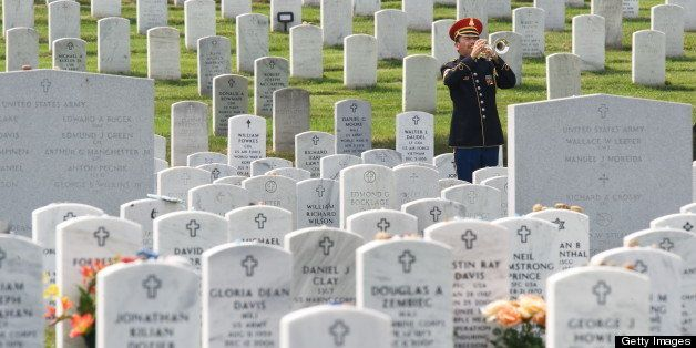 The official Bugler plays taps during the burial of US Army Specialist Anthony M. Lightfoot, of Riverdale, Ga, on August 4, 2