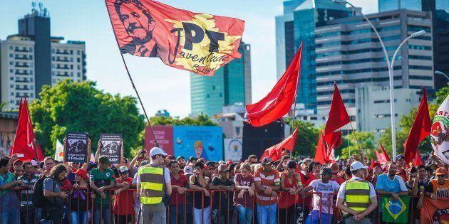 Pessoas de todo o Brasil se mantêm coladas ao gradil que delimita a área bloqueada, entoando cantos e...