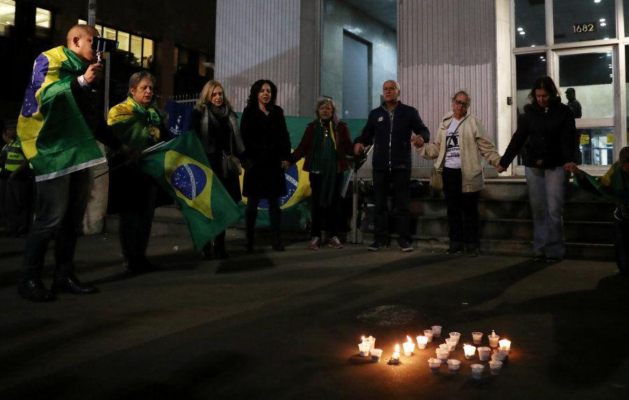 Pessoas acendem velas e fazem oração na frente da Santa Casa em Juiz de Fora