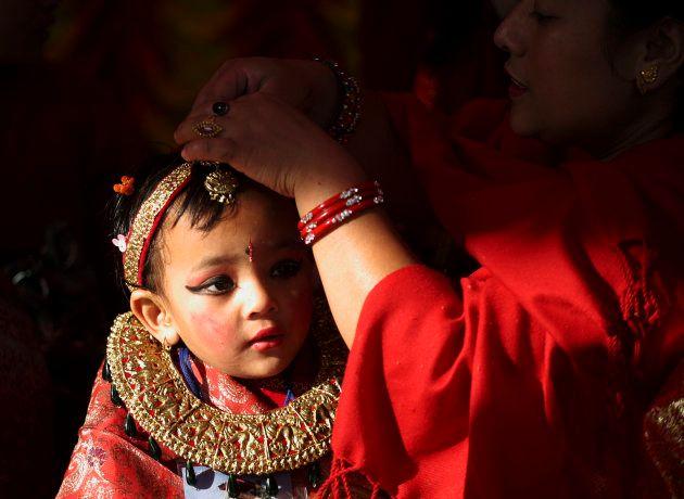 No Nepal, uma menina recebe os últimos cuidados de sua vestimenta para o ritual de seu