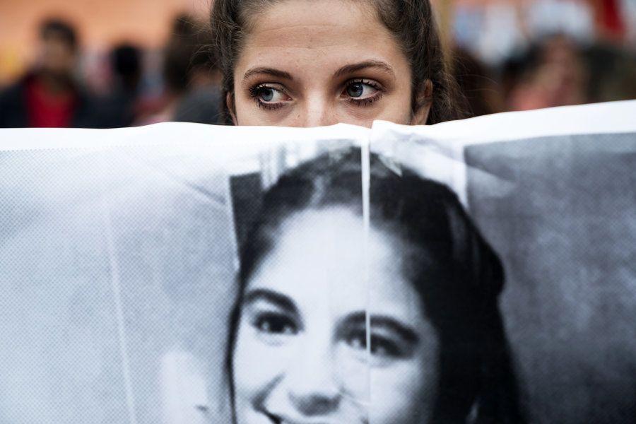 Manifestante segura cartaz com o rosto de Micaela García em protesto em Abril de