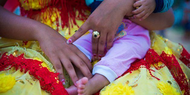 Shanya*, 15 anos, segura a filhinha de 5 meses que já está prometida para se casar com um garoto da vizinhança...