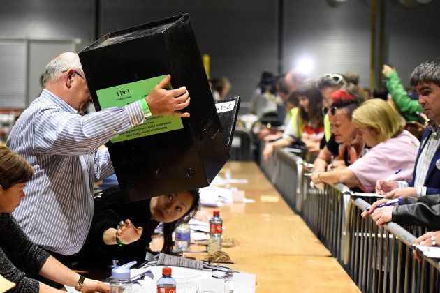 A woman checks underneath a ballot box, to make sure it has been emptied properly, as counting of the...
