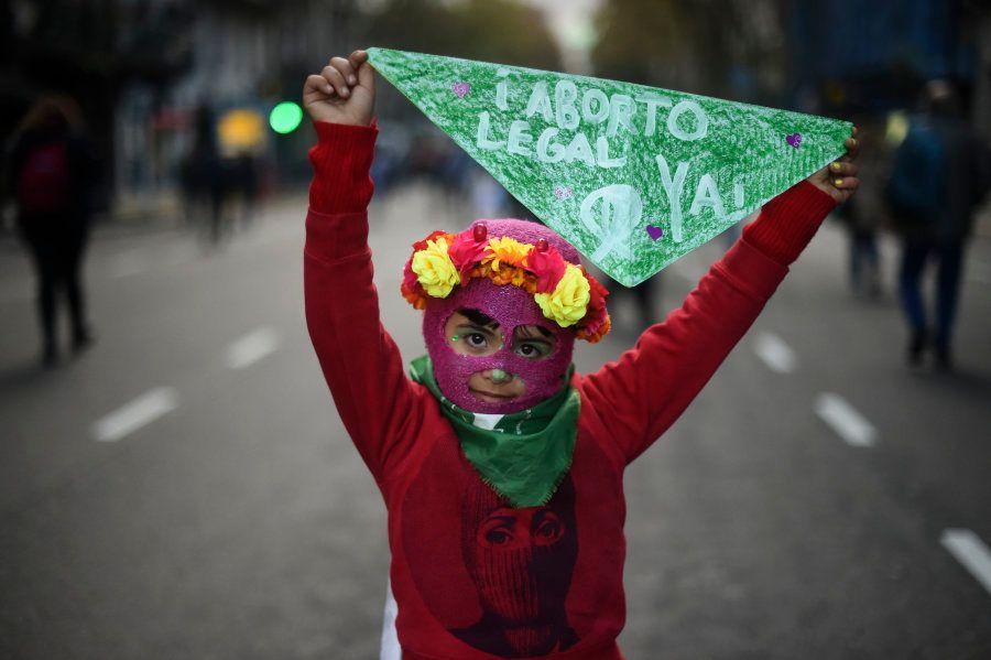 Menina ergue lenço verde com