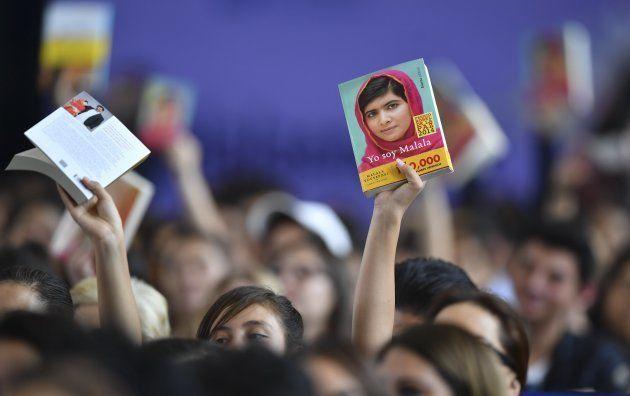 Ativistas e estudantes seguram a biografia de Malala,