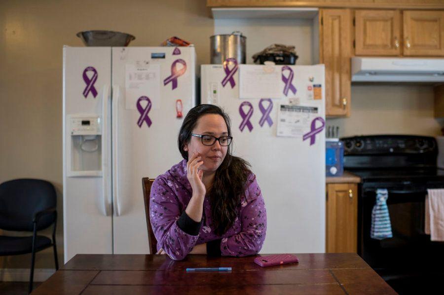 Desiree Wolfrey na cozinha comunitária do abrigo Kirkina House, decorado com fitas roxas, símbolo da...