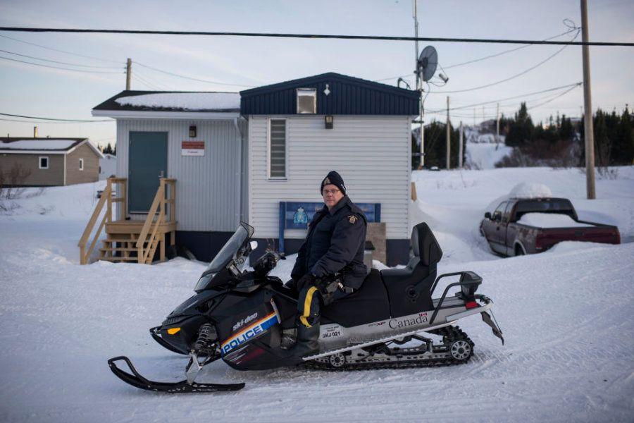 Mike McKee, um dos dois policiais de Rigolet, em sua moto de neve, na frente do posto policial do vilarejo,...