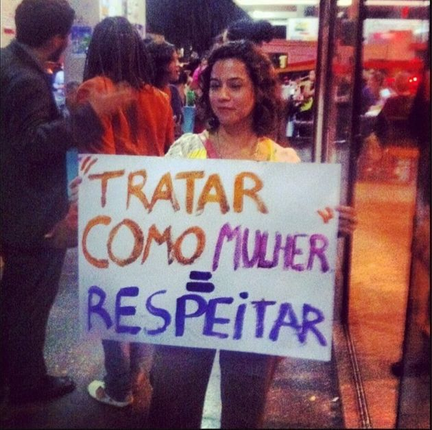 Eu, Danyella Proença, em protesto com cartaz que explica como tratar uma mulher: com