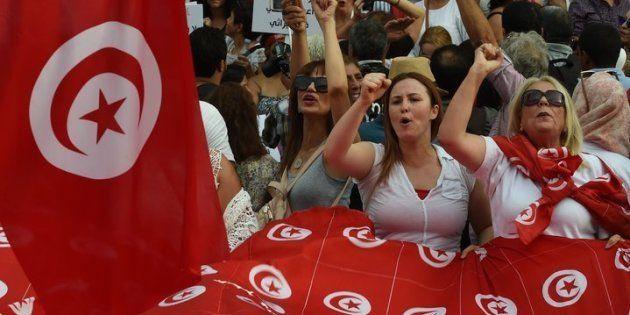 Tunisianas agitam bandeiras nacionais e gritam palavras de ordem num protesto do Dia da Mulher Tunisiana,...