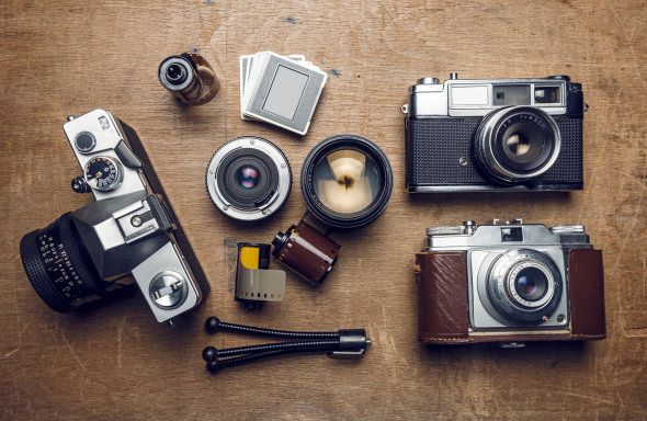 Vintage cameras and photography equipments on wood, high angle view, studio