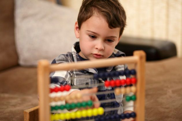 Young boy is learning basic mathematical concepts like counting, addition and