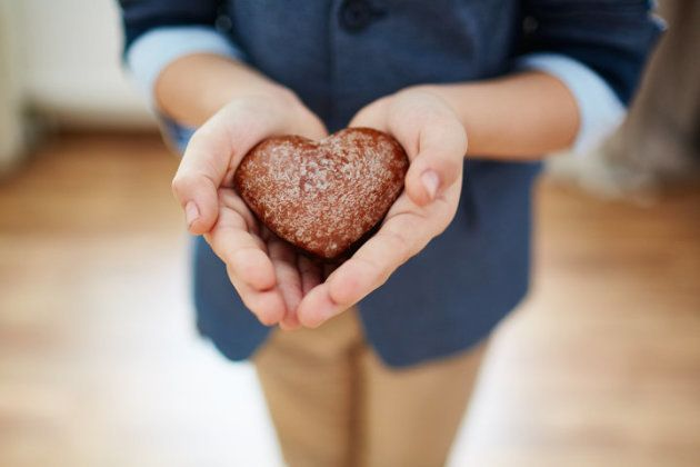Boy carefully holding heart-shaped cookie