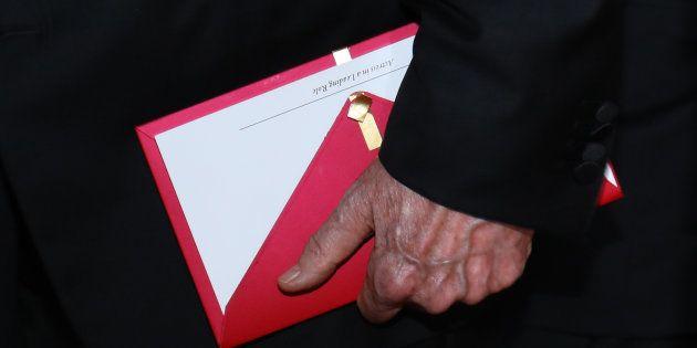 O apresentador Warren Beatty segura o evelope contendo o Oscar de 'Melhor