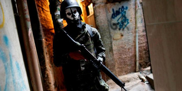 A member of the armed forces takes up position during a operation after violent clashes between drug...