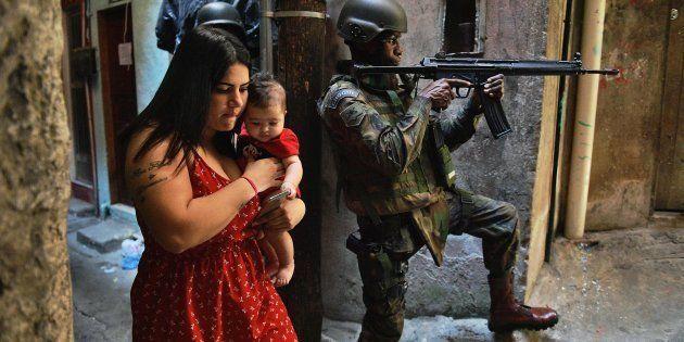 Mulher com bebê no colo na favela da Rocinha, no Rio de Janeiro, ocupada pelo