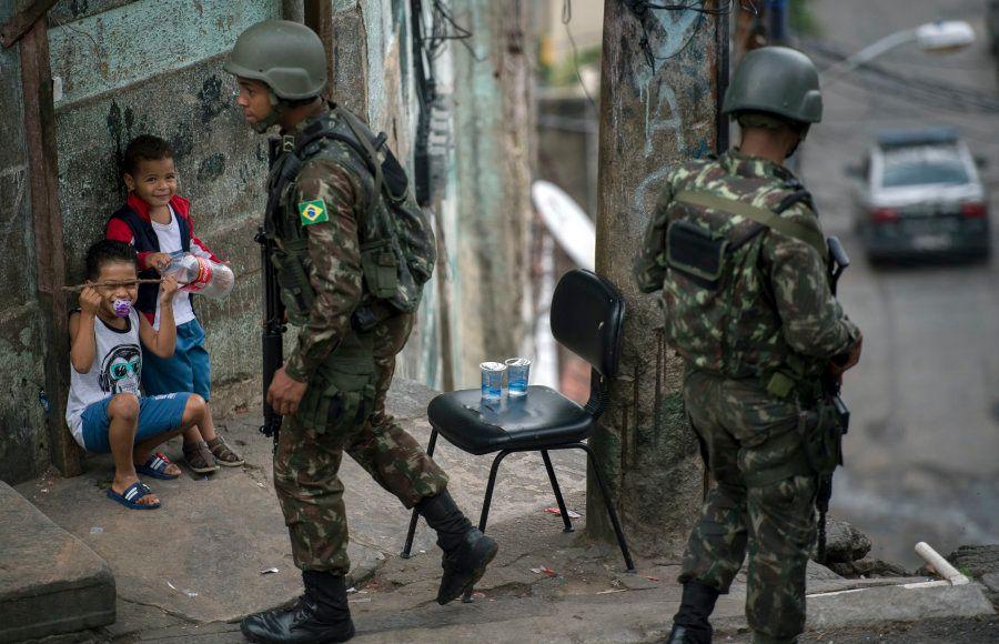 Crianças ao lado do Exército na favela São Carlos, no Rio de