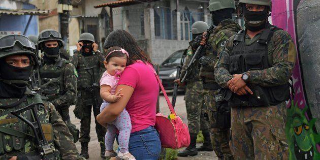 Mulher carrega criança em meio a militares na favela Vila Kennedy, no Rio de Janeiro, em fevereiro de