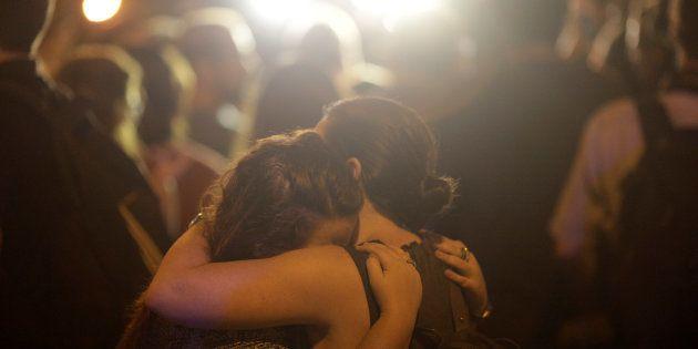 Duas mulheres se abraçam em local próximo à cena do crime, na noite desta quarta-feira (14), no Rio de