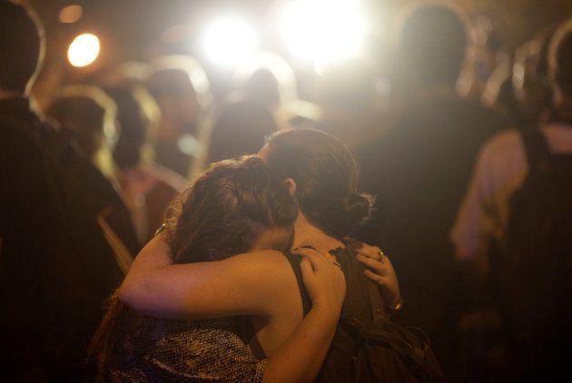 Duas mulheres se abraçam próxima à cena do crime na noite desta quarta-feira (14), no Rio de
