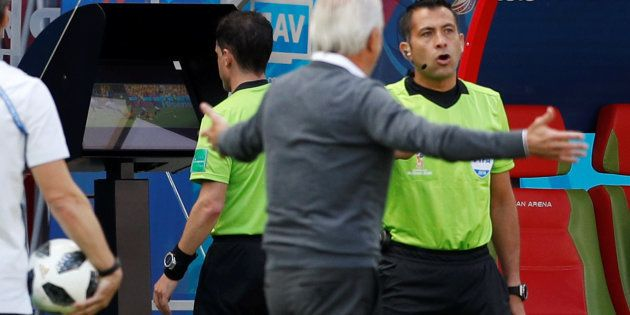 Andres Cunha observa o monitor de vídeo para, na sequência, reverter sua decisão e marcar pênalti a favor...