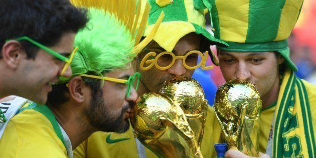 Torcedores brasileiros beijam réplicas da taça da Copa: caminho do hexa é