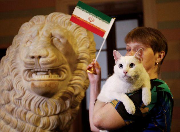 Funcionária do museu tremula a bandeira do Irã, apontado como vencedor do duelo contra Marrocos por