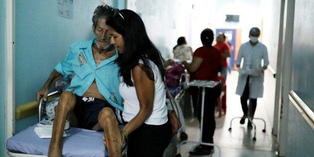 Mulher ajuda pai a se sentar em maca de hospital público de Boa Vista, em