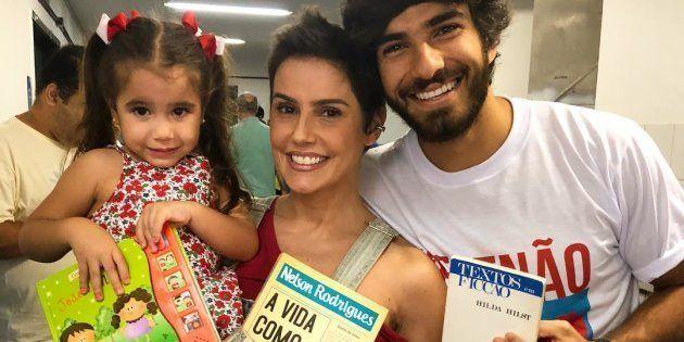 Atriz Deborah Secco e sua família posa com livros na mão ao votar no segundo