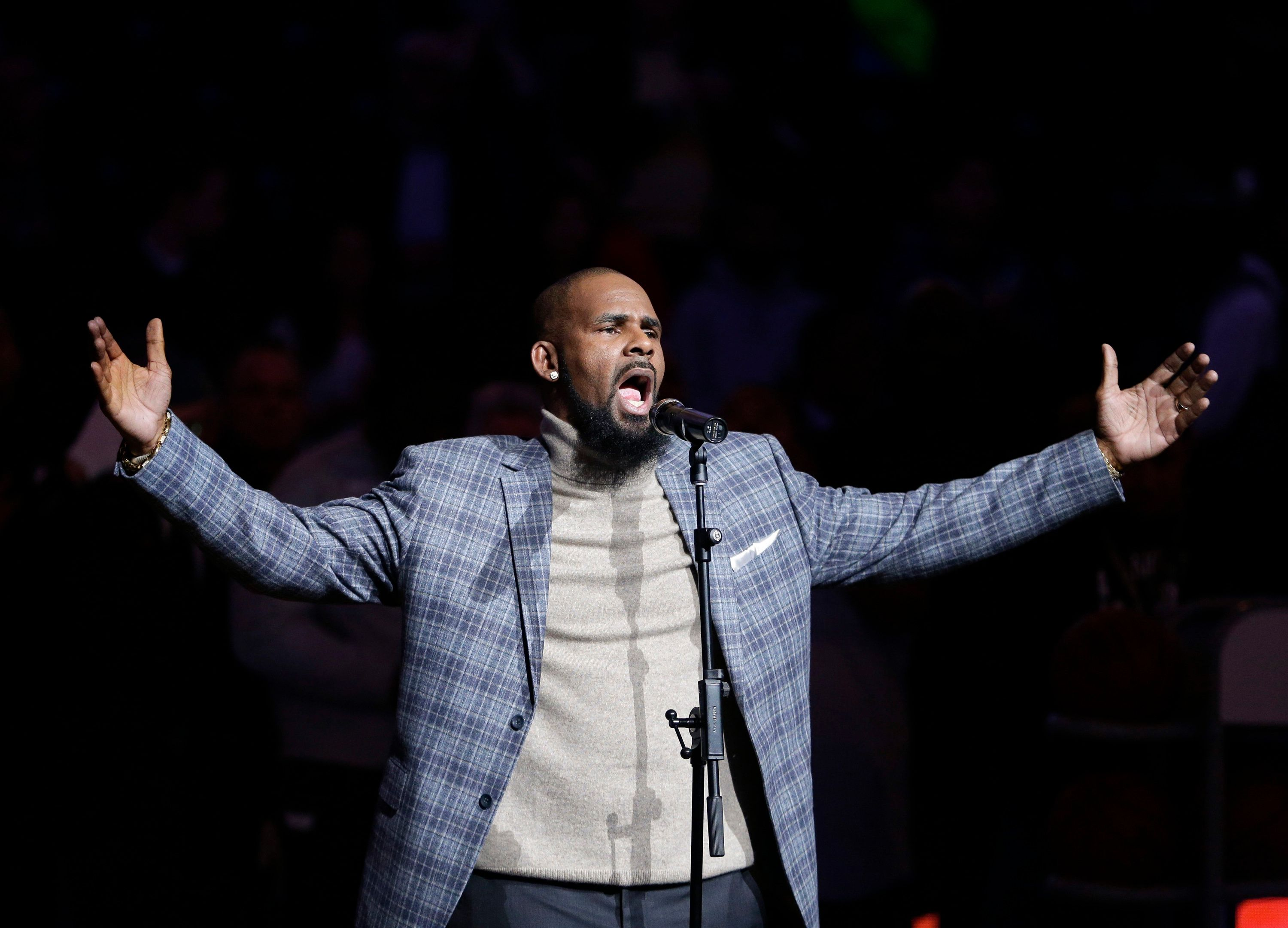 "FILE - In this Nov. 17, 2015, file photo, musical artist R. Kelly performs the national anthem before an NBA basketball game between the Brooklyn Nets and the Atlanta Hawks in New York. A screening of an upcoming documentary detailing abuse allegations against singer R. Kelly was evacuated after phone threats were made to the Manhattan location where it was being held. The New York Police Department says the threats to the NeueHouse Madison Square came in Tuesday night, Dec. 4, 2018, when it was hosting a screening of Lifetime's ""Surviving R. Kelly"" series. (AP Photo/Frank Franklin II, File)"