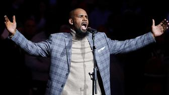 """FILE - In this Nov. 17, 2015, file photo, musical artist R. Kelly performs the national anthem before an NBA basketball game between the Brooklyn Nets and the Atlanta Hawks in New York. A screening of an upcoming documentary detailing abuse allegations against singer R. Kelly was evacuated after phone threats were made to the Manhattan location where it was being held. The New York Police Department says the threats to the NeueHouse Madison Square came in Tuesday night, Dec. 4, 2018, when it was hosting a screening of Lifetime's """"Surviving R. Kelly"""" series. (AP Photo/Frank Franklin II, File)"""