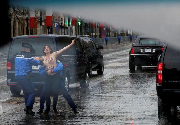 Manifestante de topless se joga em frente ao carro do presidente americano, Donald Trump, no caminho...