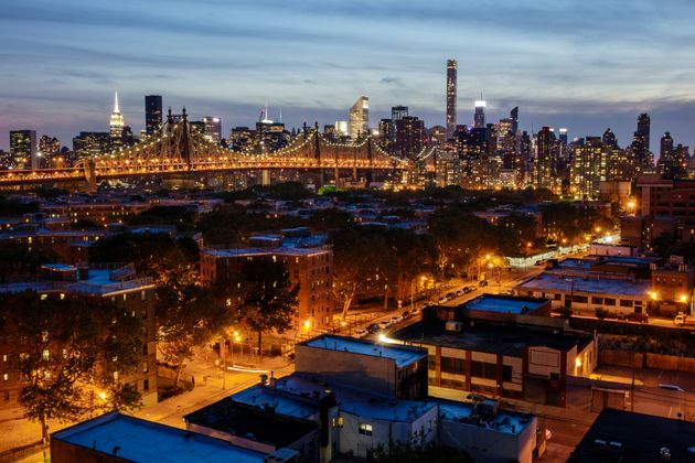 The Manhattan skyline glowing with electric power, as seen from the Long Island City side of the Queensboro