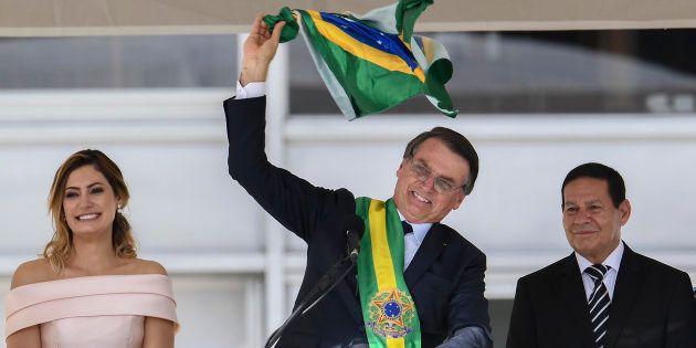 Bolsonaro tira bandeira do Brasil do bolso e acena a apoiadores durante