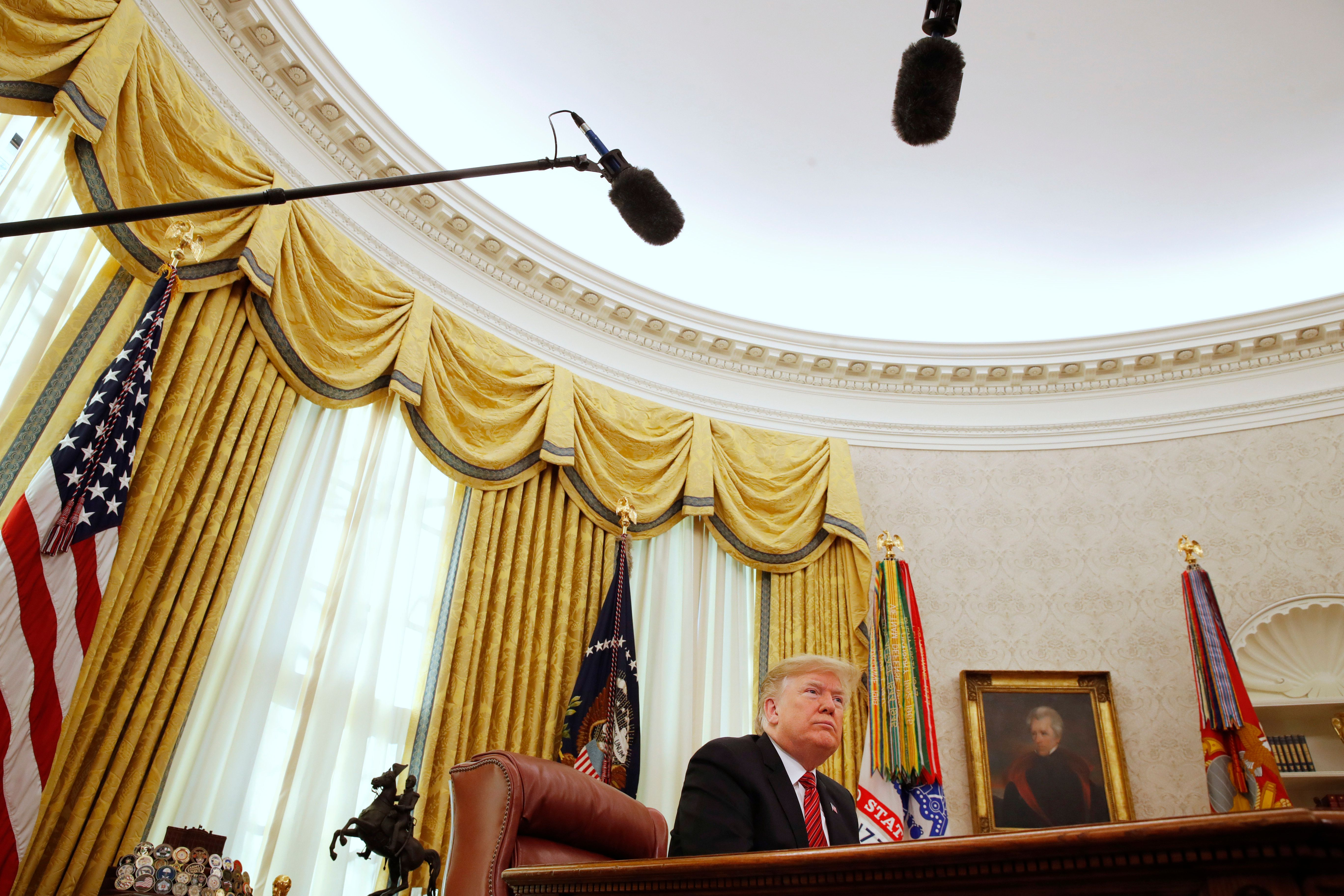 President Donald Trump listens to questions from the media after speaking with members of the military by video conference on Christmas Day, Tuesday, Dec. 25, 2018, in the Oval Office of the White House. (AP Photo/Jacquelyn Martin)