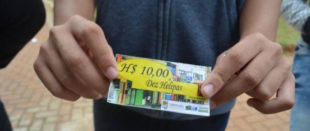 Jovem de Heliópolis mostra sua conta de $10 Helipas, moeda usada pela comunidade local nos negócios da