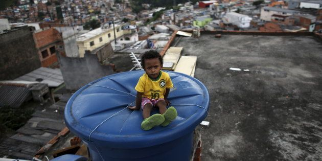 Igor, 6, sits on a water container, on the roof of his house in Brasilandia slum, in Sao Paulo, Brazil,...