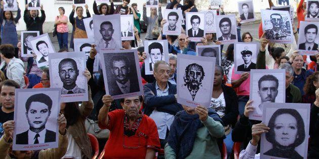 Membros da Comissão Nacional da Verdade e ativistas pelos direitos humanos protestam na antiga sede do...