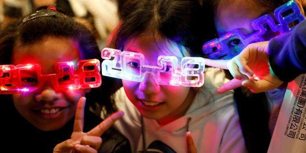 Crianças usam óculos temáticos para a chegada de 2018, em Hong Kong, na