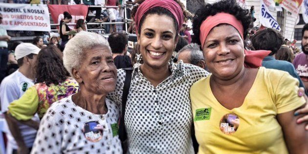 Marielle Franco posa ao lado de duas eleitoras da mesma família e de gerações