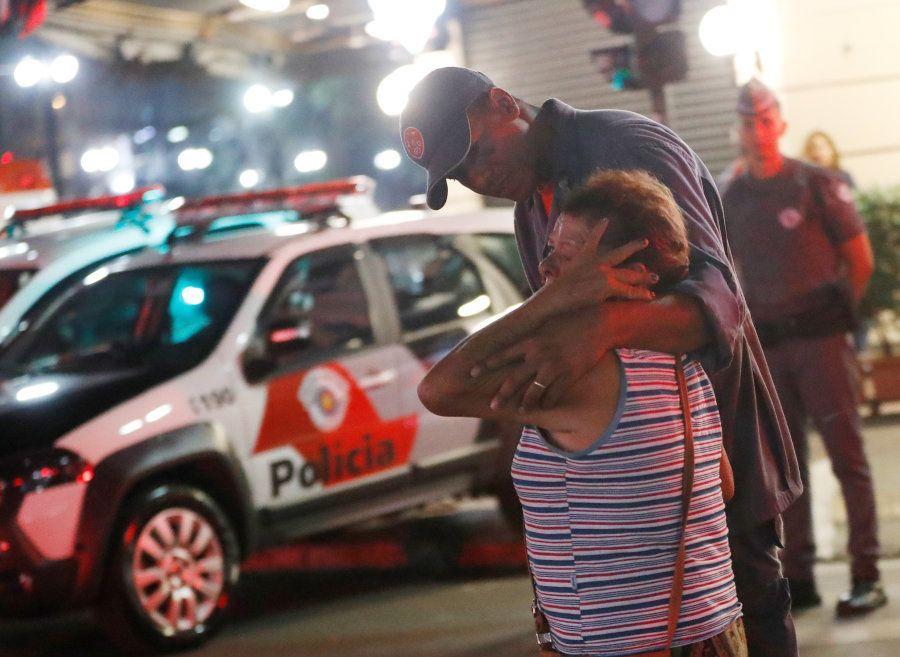 Policial conforta uma mulher perto do local onde um prédio desabou no centro de São Paulo. Edifício era...