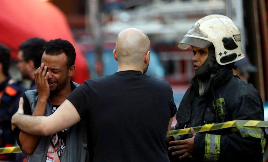 Oficiais confortam um homem perto do local onde um prédio desabou com mais de 90 famílias no centro de...