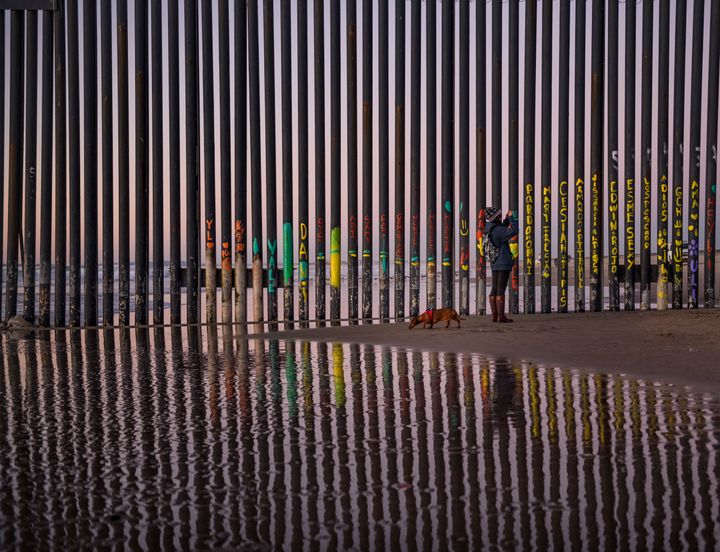 A woman takes a snapshot by the border fence between San Diego and Tijuana, as seen from Mexico, on Thursday.