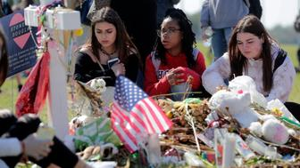 Students Gabrielle Benzaken, left, Brielle Pitterson, center, and Falynn Kiernan, right, sit at makeshift memorial for Martin Duque, one of the victims of the mass shooting at Marjory Stoneman Douglas High School, at Pine Trails Park, Wednesday, March 14, 2018, in Parkland, Fla. People gathered at the park as part of a nationwide protest against gun violence, following the massacre of 17 people at Marjory Stoneman Douglas High School in February. (AP Photo/Lynne Sladky)