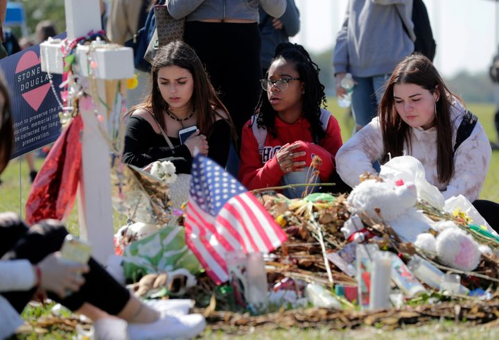 Students sit at a makeshift memorial for one of the victims of the mass shooting at Marjory Stoneman Douglas High School, Mar