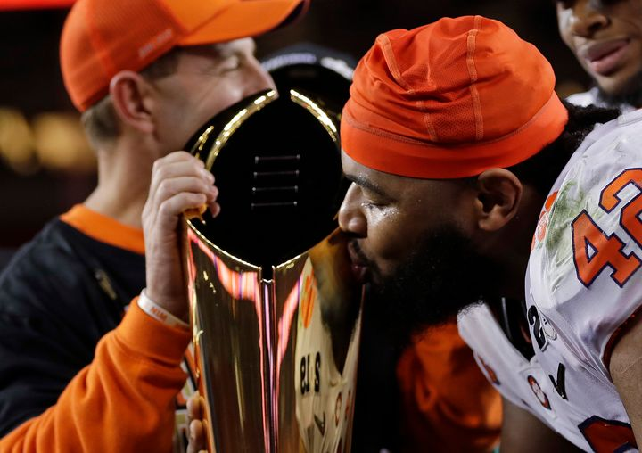Clemson defensive lineman Christian Wilkins kisses the trophy after winning the championship Monday night.