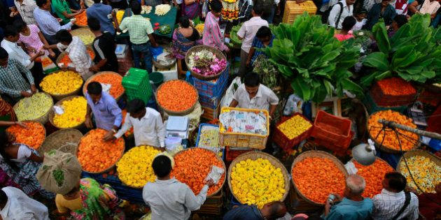 Indians crowd a market selling marigold flowers early morning on Diwali, the Hindu festival of lights,...